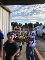Junior football players and cheerleaders greet students in car rider line