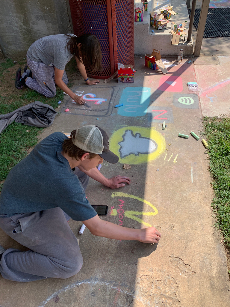 Freshmen students chalk the sidewalks with art